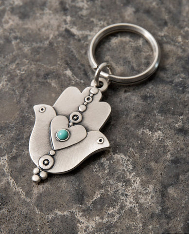 "An extraordinarily beautiful keychain with a rare design, coated in sterling silver. On one side of the Hamsa is a dove inlaid with a turquoise colored Swarovski crystal. Engraved on top is the Kohen's blessing ""May the Lord bless you and keep you safe"". On the other side of the Hamsa are two doves looking in opposite directions, with a heart in between them that is also embedded with a turquoise stone. A keychain that is all beauty and blessings. The Hamsa's blessing for good luck, the doves blessing for p"