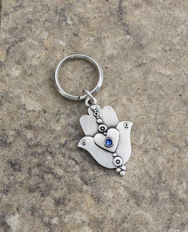 "A extraordinarily beautiful keychain with a rare design, coated in sterling silver. On one side of the Hamsa is a dove inlaid with a blue colored Swarovski crystal. Engraved on top is the Kohen's blessing ""May the Lord bless you and keep you safe"". On the other side of the Hamsa are two doves looking in opposite directions, with a heart in between them that is also embedded with a blue stone. A keychain that is all beauty and blessings. The Hamsa's blessing for good luck, the doves blessing for peace and lo"