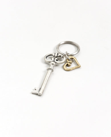 The key to the heart - because hearts and keys have gone together since the beginning of time. A charming and exciting keychain, the key is coated in sterling silver and has a classic design. The heart hangs next to the key, coated in golden brass. The keyring is strong and reliable. This is a timeless and classic present, suitable for any man or woman, in any occasion you wish to grant the gift of love.  Length: 10 cm  Width: 3 cm