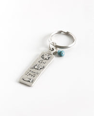 "A keychain with a classic look, designed as a two-sided rectangular plate. Written on one side is the passage ""May the Lord bless you and keep you safe"", and on the other side appear decorations of good luck - a Star of David, a Hamsa with an eye, and a fish. In between the charms the words ""Luck"" and ""Hamsa on you"" are written. At the top of the rectangle hang two round turquoise colored stones, to complete the perfect look.  The keychain is coated in sterling silver and is strong and reliable.  A great pr"