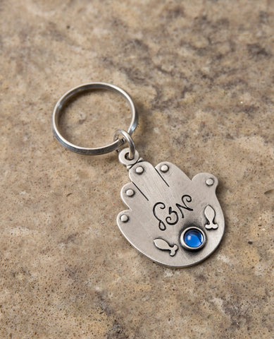 "An exciting double-sided Hamsa keychain. On one side of the Hamsa the words ""Good journey and safe travels!"" are written. Written on the other side is the word ""Luck"" with a blue stone embedded underneath, and next to it an embossed image of two fish. The Hamsa is coated in sterling silver and is strong and reliable to accompany your loved ones throughout the entire journey. A charming and loving gift for anyone about to embark on a trip in the voyage of life. A present that will leave our loved ones with a"