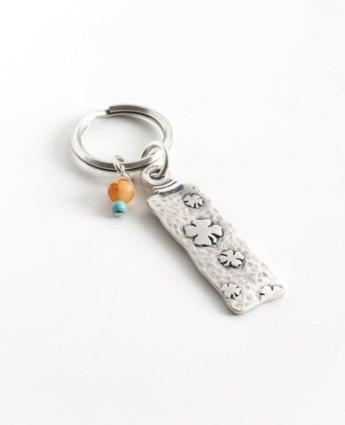 "The gift that is most fun to give! A classically designed keychain - for him or for her. Shaped like an elongated rectangle with the words ""Follow Your Dreams"" on one side and embossed leaves decorating the other side. At the top of the keychain are two differently colored beads in the charming mix of orange and turquoise. The keychain is coated in sterling silver and is strong and reliable. A great gift to give to someone you love, anyone beginning a journey, or simply as a reminder that most important is"