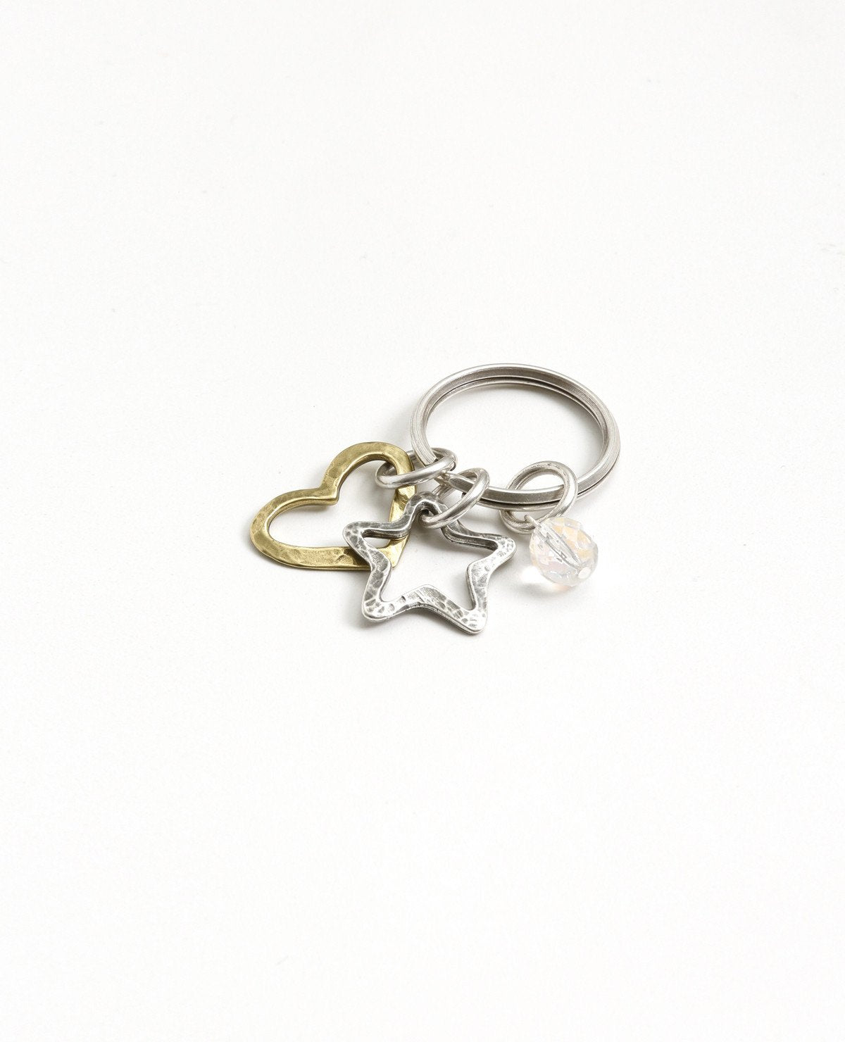 An original and special keychain, designed as a ring upon which hang a heart, a star and a crystal-like bead. The keychain is coated in sterling silver except for the star which is coated in brass, making for a magnificent color combination. Makes a fun gift, for her or him, for any occasion you wish to bring joy with a special present.  Length: 6 cm  Width: 3 cm