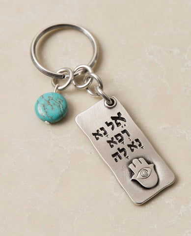 "A beautiful and excitingly designed keychain, the content of which was taken from a prayer by Moses for the health of his sister, and it is in fact a prayer for good health. Shaped as a rectangular plate that has the sentence ""Please, God, heal her"" written in Hebrew on one side, and underneath an embossed image of a Hamsa with an eye. The other side contains blessings, in both English and Hebrew, for quick recovery, good health, and longevity. Next to the plate hangs a pretty turquoise stone. The keychain"