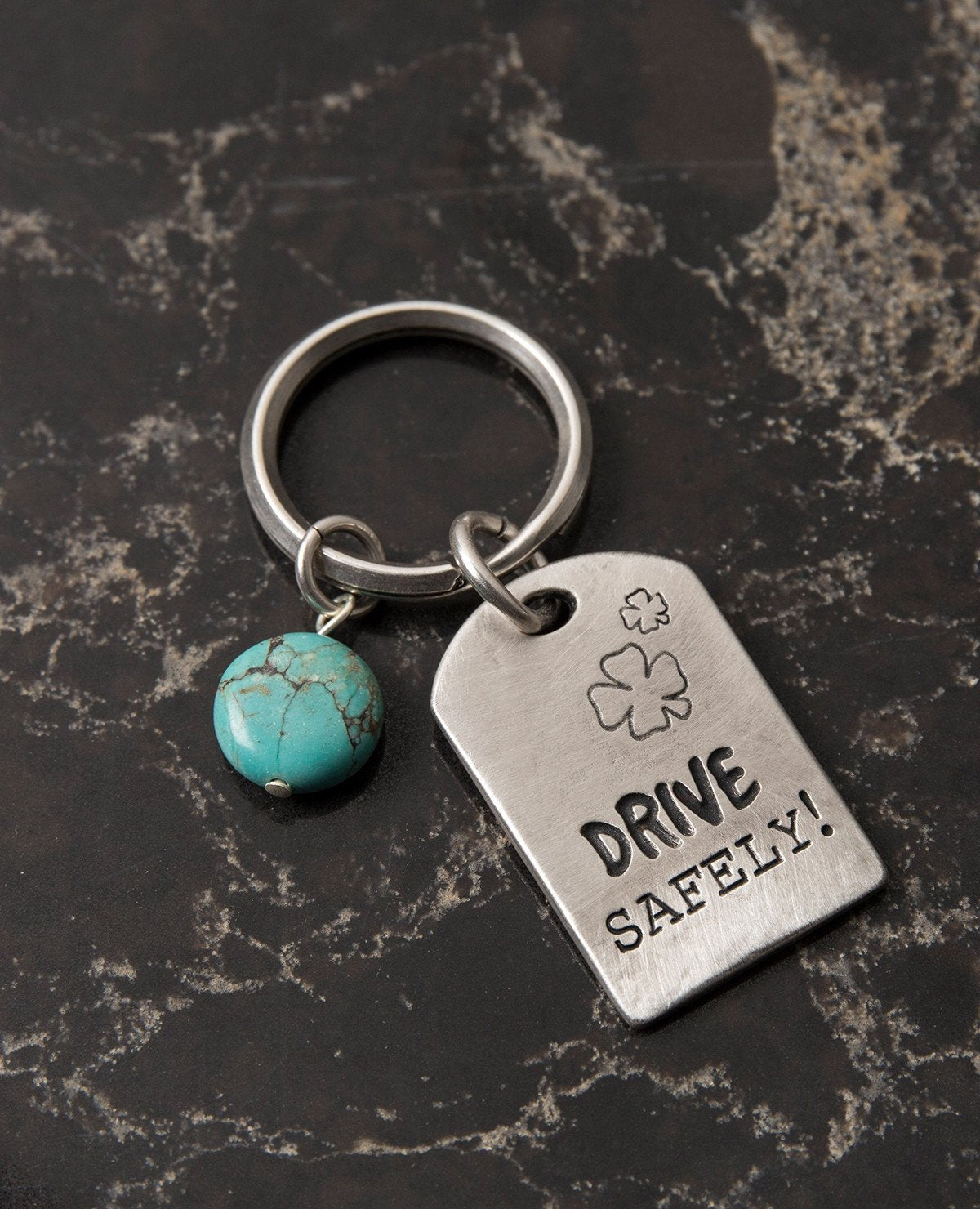 "Drive carefully! Somebody loves you and cares about you. An impressive and excitingly designed keychain in the shape of a rectangular plate. One side has the words ""Drive Safely"" written on it, and on the other side the words ""Someone loves you"". Next to the plate hangs an impressive round turquoise stone. The keychain is coated in sterling silver and is strong and reliable. An exciting gift for him or for her with an important reminder: take care when driving, because somebody loves you.  Length: 7 cm  Wid"