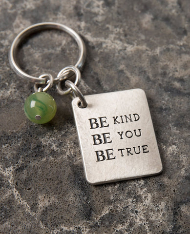 "A keychain that is all charm, beauty and carries a very human message. Designed as a rectangular plate with the words ""Be Kind Be You Be True"" written in English on one side. The other side has an embossed image of a wide treetop and roots. Next to the plate hangs a stunningly beautiful green stone. The keychain is coated in sterling silver and is strong and reliable. A great gift for him or for her, here or anywhere, with the deepest and simplest message: be generous, be who you are, be real. This signific"