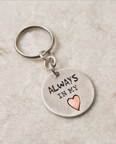 "A keychain that directly touches the heart. Designed as a circle coated in sterling silver, one side has an embossed heart coated in brass with the words ""Always In My Heart"" written on it. The other side has drawings of tiny hearts all bunched together on the right side of the heart. The keychain is strong and reliable. Makes an exciting gift that says it all: always in my heart! Next to the beat of your heart there is always room for the heartbeat of your lover, best friend, mother, father, family member."