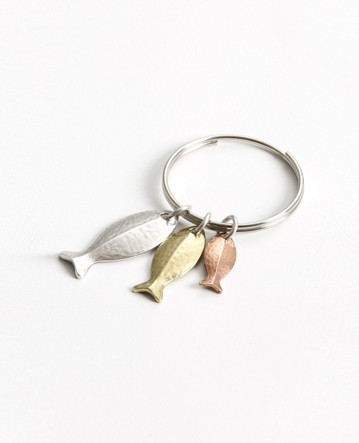 A stunning keychain that comes with a smile and a triple blessing. Designed in the shape of a ring upon which hang three cute fish in different sizes, coated in three different metals and colors: silver, gold and copper. The fish symbolizes fertility, abundance and luck (in Hebrew fish spelled backwards is luck). A fun gift full of beauty, motion and lots of good luck! Grant it with love to anyone important which you hold dear, and to anyone who you always wish luck, abundance and blessing. The keychain is