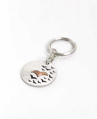 "A keychain with an inspiring message: live the moment! What has happened is history, and what will be is a mystery. So all that is left is to experience the moment in its entirety. The keychain is designed as a round hanger with the words ""Live In The Moment"" written on one side, and on the other an embossed image of a large bird coated in copper, with black birds flying around it. All this on a backdrop coated in sterling silver. The keychain is strong and reliable. Makes a great gift with a message for He"