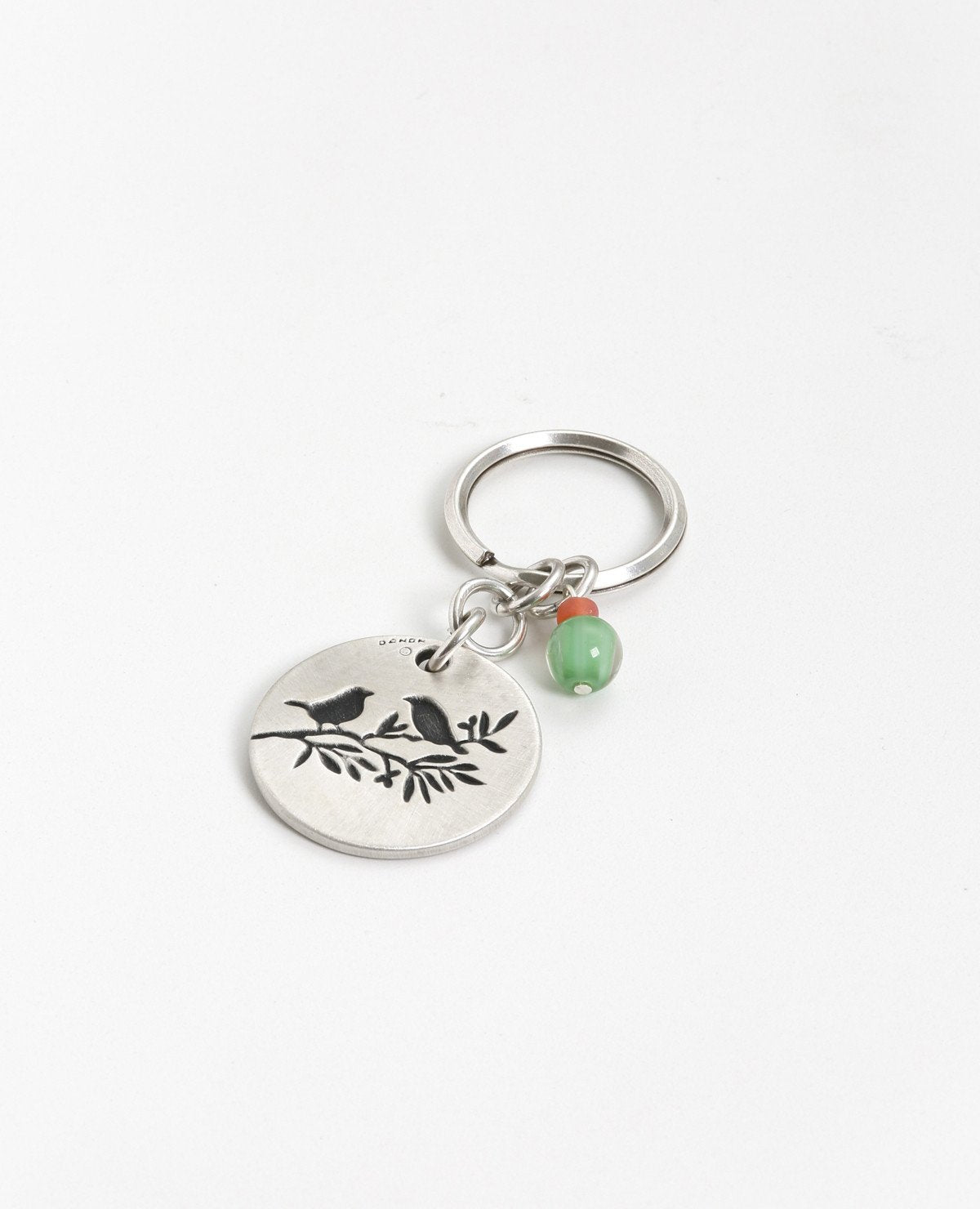 "The freedom to be exactly who you are! An authentic and captivating keychain that you should always have ready to hand to someone special. The keychain is designed as a circle with the words ""Freedom is a state of mind"" written on one side, and on the other a drawing of a pair of birds perched on a tree branch. The circle is connected to the keyring with three strong rings. The top one of the three has charming green and orange beads hanging from it. Simple, precise, beautiful and oh so significant. The key"