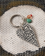 "A one of a kind keychain that crosses borders and brings hearts together. Designed as an elongated heart coated in sterling silver, upon which the word ""Love"" is written in different languages. Hanging on the keyring next to the heart are two colorful beads that add beauty and intrigue. The keychain is strong and reliable. Makes a great gift of love, anywhere and at any time, so that in the moment of truth, you won't find yourself at a loss for words...  Length: 9 cm  Width: 3 cm"