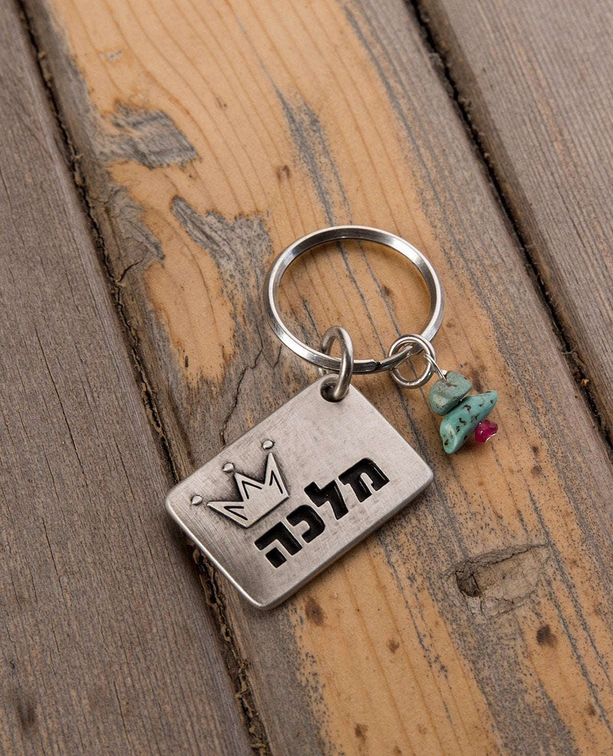 "A majestic and meaningful keychain, intended specifically for your queen. Designed as a rectangle coated in sterling silver, with the word ""Queen"" written on one side, along with an embossed crown. On the other side is an embossed crown. Next to the rectangle hang three colorful beads. The keychain is strong and reliable. Makes a great gift that says it all, for the queen who is only yours.   Length: 3 cm  Width: 4 cm"