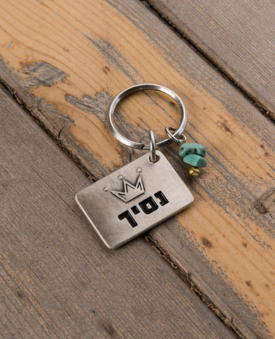 "A simple and charming keychain, intended specifically for your prince. Designed as a rectangle coated in sterling silver with the word ""Prince"" written on one side, along with an embossed crown. On the other side is an embossed crown. Next to the rectangle hang two turquoise colored beads and a gold colored bead. The keychain is strong and reliable. Makes a great gift to embrace all the princes in your kingdom with a hug.   Length: 3 cm  Width: 4 cm"