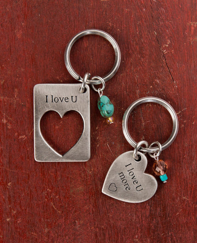 "A visually remarkable and extremely romantic pair of keychains. One is designed as a rectangle with a missing piece in the shape of a heart with the words ""I Love U"" written on top. The other keychain is designed in the shape of a heart and has the words ""I Love You More"" written on it, perfectly completing the piece on the other keychain. Each one of the keychains is decorated by two colorful beads. The keychains are coated in sterling silver and are strong and reliable.  A perfect and romantic gift for an"