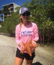 Evelyn wearing the fin therapy pink performance shirt holding a star fish