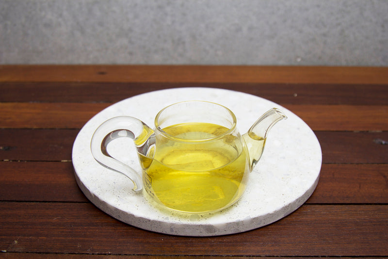 Yellow brew in a glass tea pot on a marble and wood top.