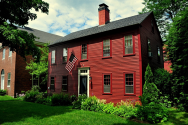 Traditional colonial red exterior and trim with cream front door trim and black door