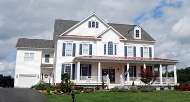 traditional white colonial house with red accent features