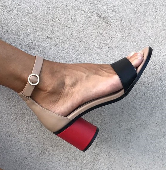 ANNY NORD sandal, style name 24-7, beige, combination of beige, black and poppy red leathers. Round gold meteal buckle and cylinder shaped heel. Photo with foot.