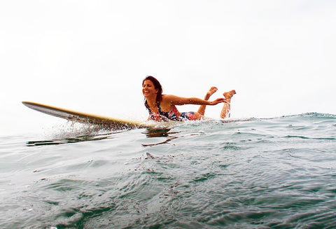 Woman paddling for a wave