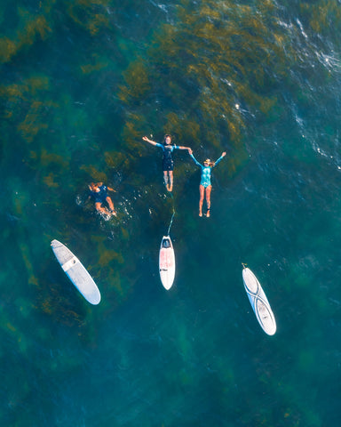 Drone image of people in water next to their surfboards