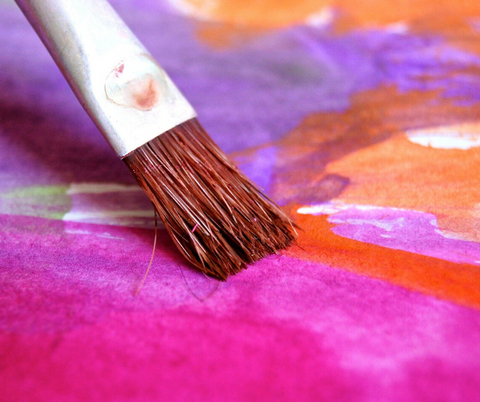 Paint brush with purple and orange painted background