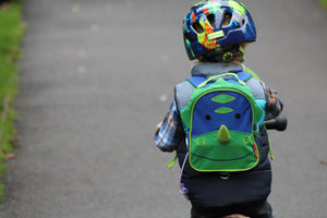 A child wearing a feeding tube backpack