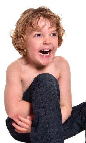 Boy with a mickey button looking to the right of the picture and laughing