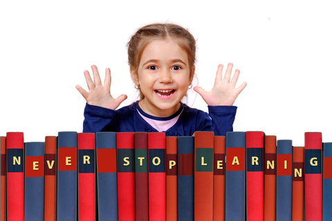 Girl peering over a line of books with her hands in her air