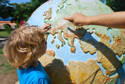 Boy looking at a globe and pointing to a country