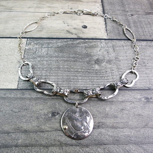 handmade sterling silver necklace with etched bird pendant