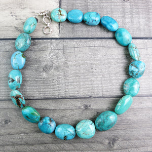 Turquoise stone necklace with sterling silver t-bar and extender rings laid out