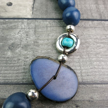 close up of a blue coloured vegetable ivory disc on a statement necklace