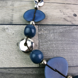 close up of vegetable ivory and silver covered clay beads on blue statement necklace