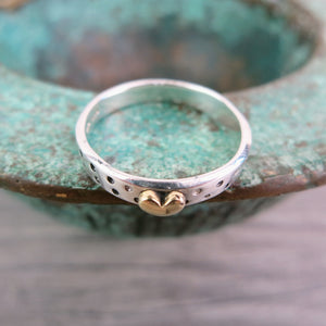 view from above of silver band ring with brass heart and dotty detail