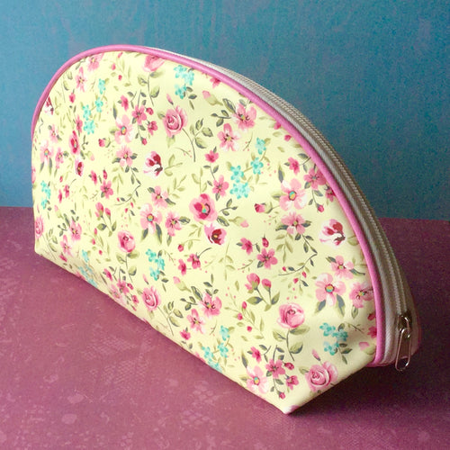 Pretty floral patterned wash bag with a curved top and two sections inside.