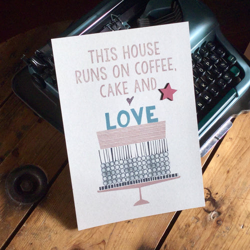 'This house runs on coffee, cake and love', printed on thick grey card with an added wooden star.
