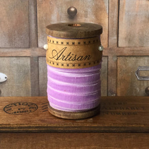 Vintage style, lilac velvet ribbon on a wooden bobbin.