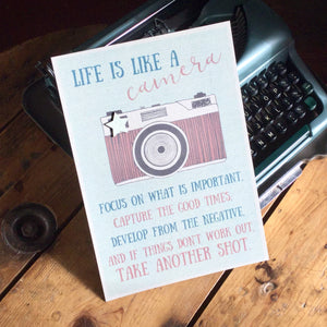 'Life is like a camera, focus on what is important, capture the good times, develop from the negative, and if things don't work out, take another shot', printed on thick grey card with an added wooden star.