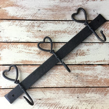 Simple wrought iron coat hooks with a lovely heart design on each of the three hooks.