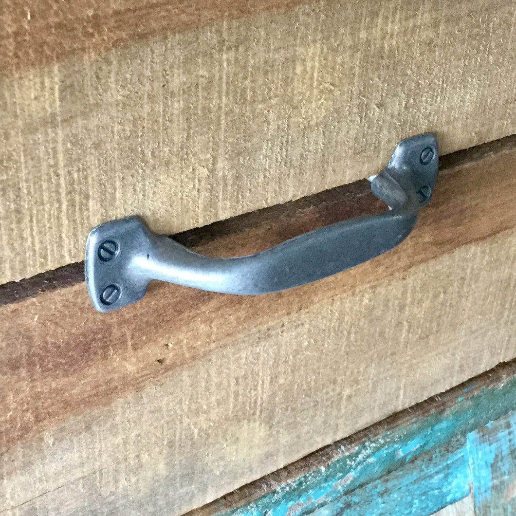 Metal drawer handle with an antique finish.