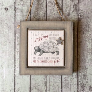 wooden plaque with a Tortoise illustration and text I gave up jogging...