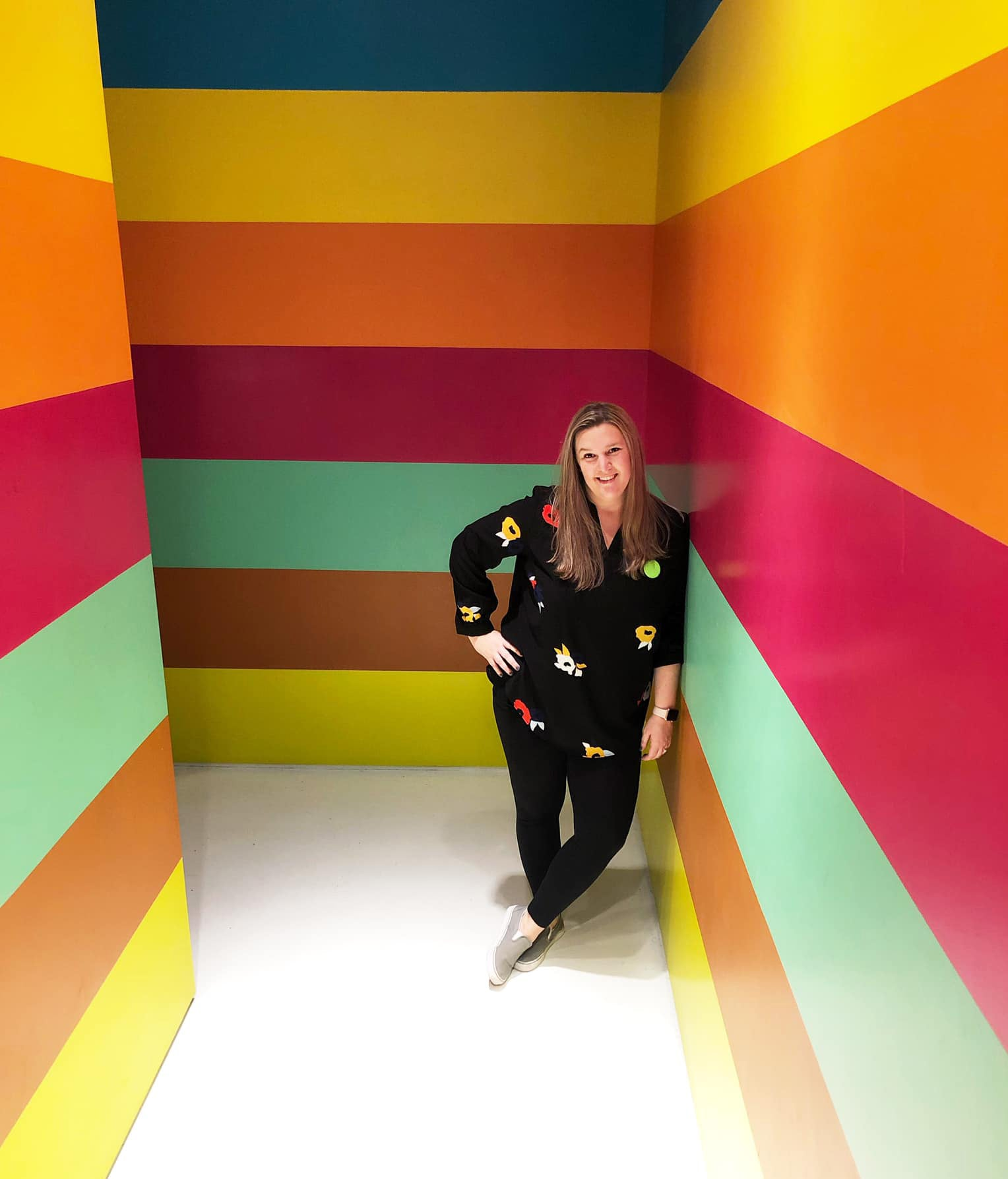 The owner of Knotty Cards, Casey Sweeney, posing against a colorful striped wall.