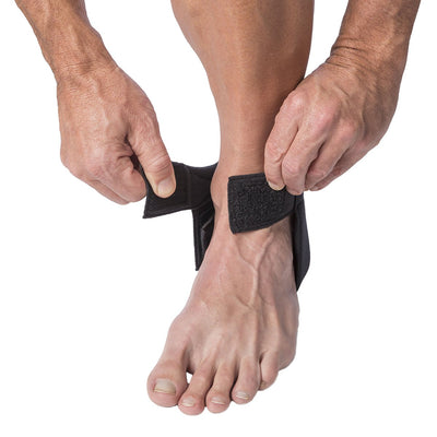 Man putting on foot the Cho-Pat Achilles Tendonitis Strap