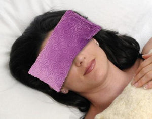 Woman's face with eye pillow over eyes -violet purple swirl velour