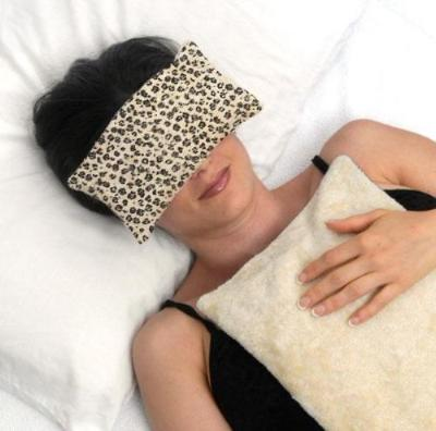 Woman's face with eye pillow over eyes -black snow leopard print on creamy white faux fur background