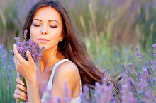 Woman holding bouquet of lavender flowers standing in a field of lavender flowers