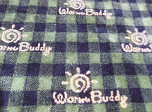 Warm Buddy logo printed on forest green and black plaid fabric square