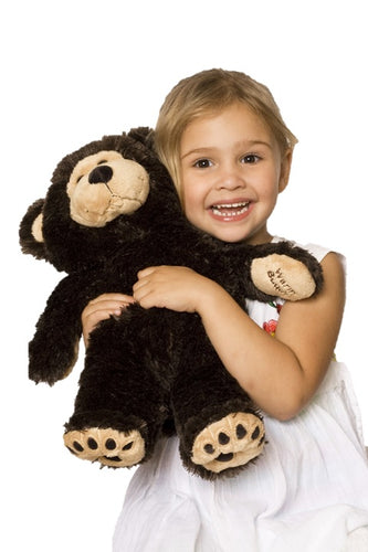 Smiling young blonde girl in white dress holding a large chocolate brown & tan therapeutic teddy bear with Warm Buddy embroidered on left paw & bear print embroidered feet