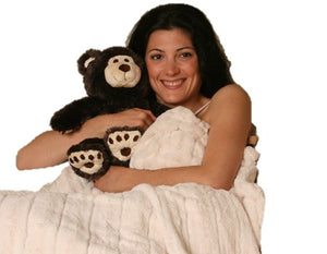 Woman covered in cream fur blanket holding and large black & white teddy bear